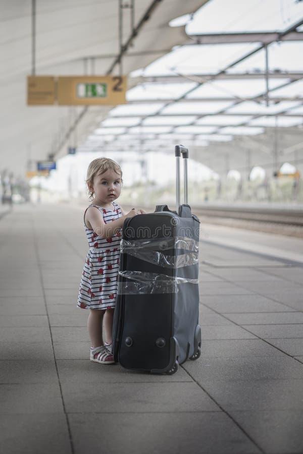 Weinig zoet meisje met een grote reiskoffer op een verlaten rai stock afbeeldingen