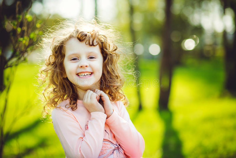 Weinig zonnig meisje glimlacht in het park royalty-vrije stock fotografie