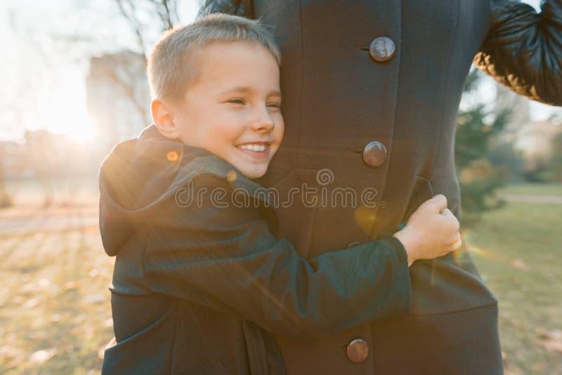 Weinig zoon die zijn moeder, jongen koesteren die, zonnige dag in het park, gouden uur glimlachen stock afbeeldingen