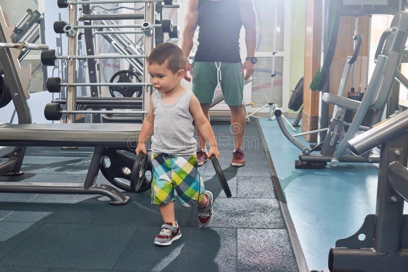 Weinig zoon die zijn vader bij de opleiding in gymnastiek helpen die zware domoren dragen stock foto's