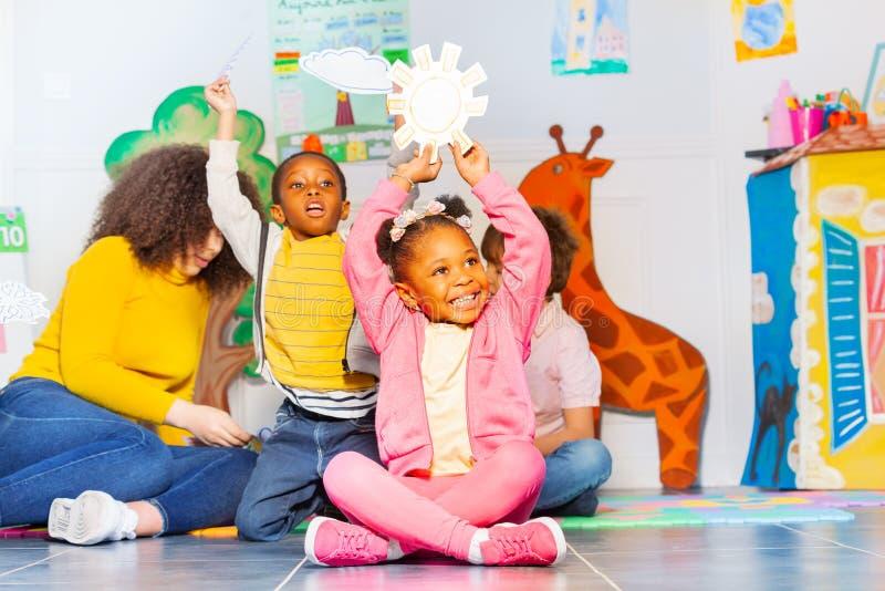 Weinig zwart meisje toont zonnige weerkaart in klasse royalty-vrije stock afbeelding
