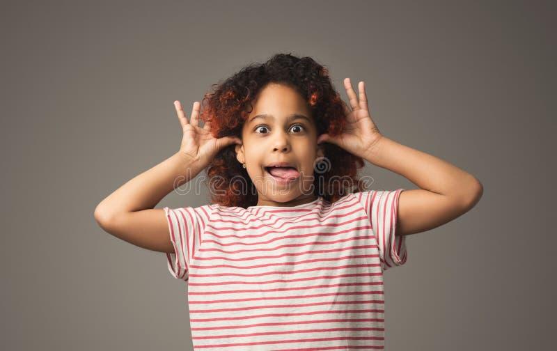 Weinig zwart ongehoorzaam jong geitje toont tong in protest stock afbeeldingen