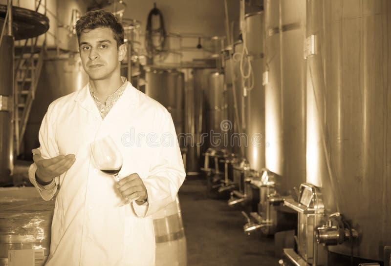Weinkellereitechniker, der mit Wein aufwirft lizenzfreie stockbilder