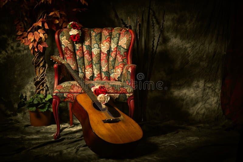 Weinlese-Akustikgitarre, die am antiken Stuhl sich lehnt stockfoto