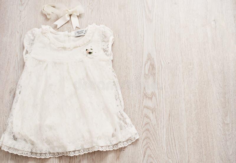 Weinlese-Baby-weißes Spitze-Kleid und Bogen-Stirnband auf hellen Gray Wodden Background Draufsicht, Kopienraum stockfoto