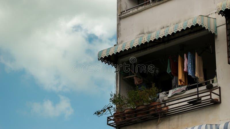 Weinlese-blaues Balkon-Fenster mit bunter Kleidung und Blumentöpfen lizenzfreie stockfotos