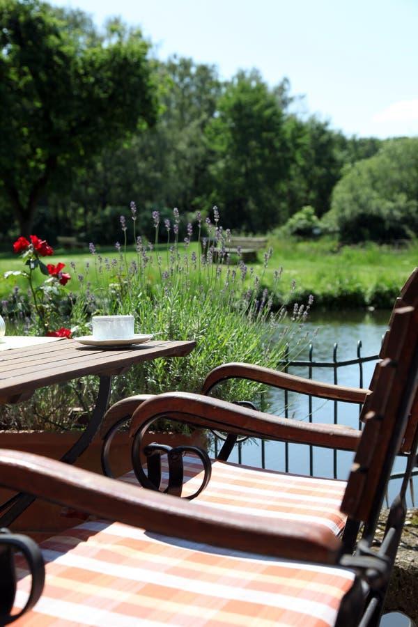 Weinlese-Couchtisch mit Stühlen an der Wasser-Bahn lizenzfreie stockfotografie