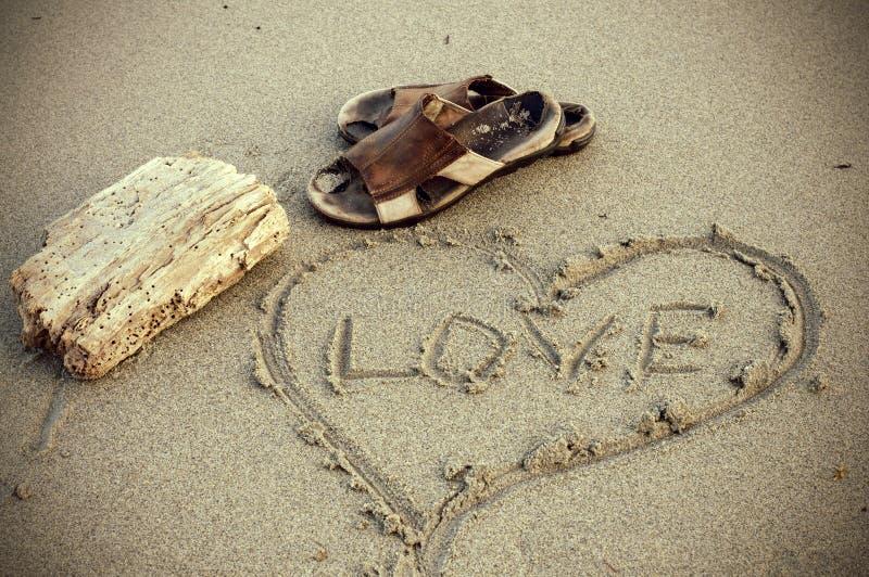 Weinlese, die Sepia-lederne Sandale und Liebes-Mitteilung im Sand schaut lizenzfreie stockfotos