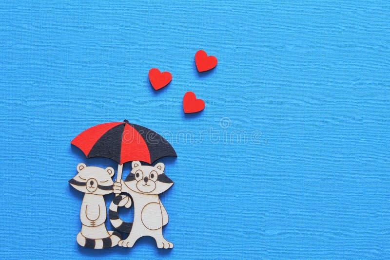 Weinlese, die stilisierte Figürchen von Liebhaberwaschbären unter Regenschirm mit roten Herzen auf hellem blauem Hintergrund beza lizenzfreies stockfoto