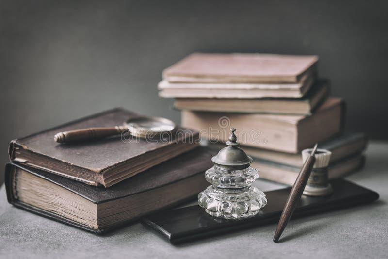 Weinlese eingestellt mit antic Büchern, altes Briefpapier, hölzerner Stift, Tintenfaß, Vergrößerungsglasnahaufnahme auf Schreibti stockbild