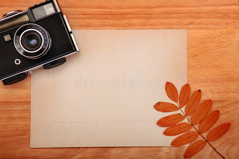 Weinlese-Foto-Kamera und Papier lizenzfreie stockbilder