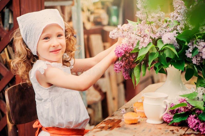 Weinlese gekleidetes Kindermädchen, das im Frühjahr Kuchen mit Blumen auf Gartenteeparty verziert stockbild