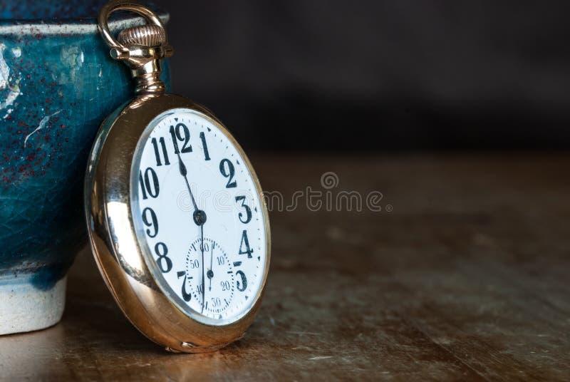 Weinlese-goldene Taschen-Uhr, die auf einem Holztisch stillsteht lizenzfreie stockfotografie