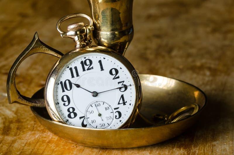 Weinlese-goldene Taschen-Uhr, die in einem Messingkerzenleuchter-Halter stillsteht stockfotografie