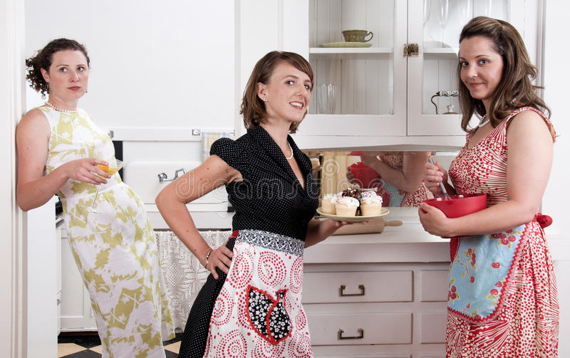 Weinlese-Hausfrauen, die kleine Kuchen und den Tratsch backen stockbilder