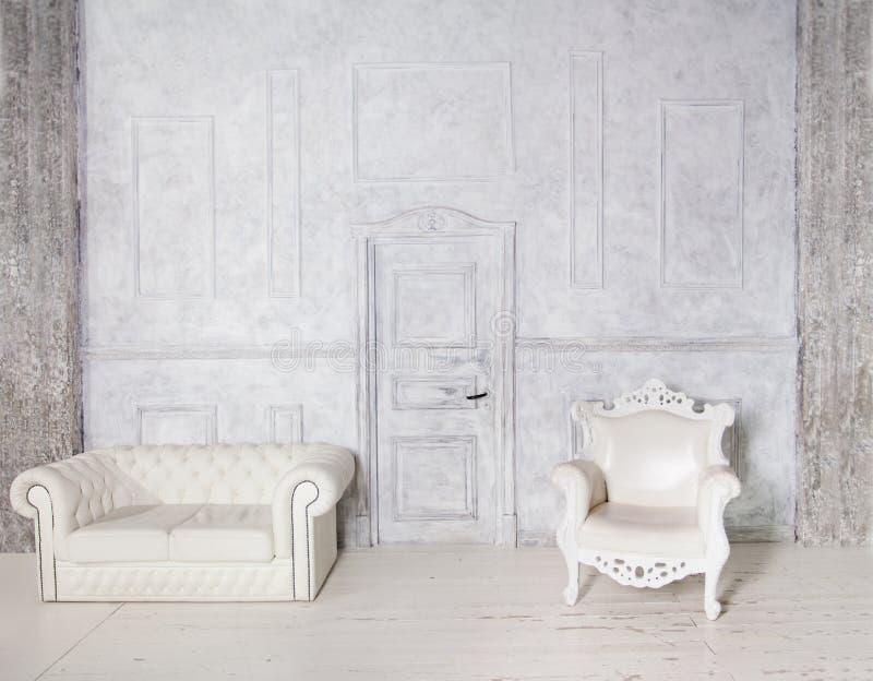 Weinlese-Innenraum mit Sofa, Lehnsessel, Stuck-Wand und Tür lizenzfreies stockfoto
