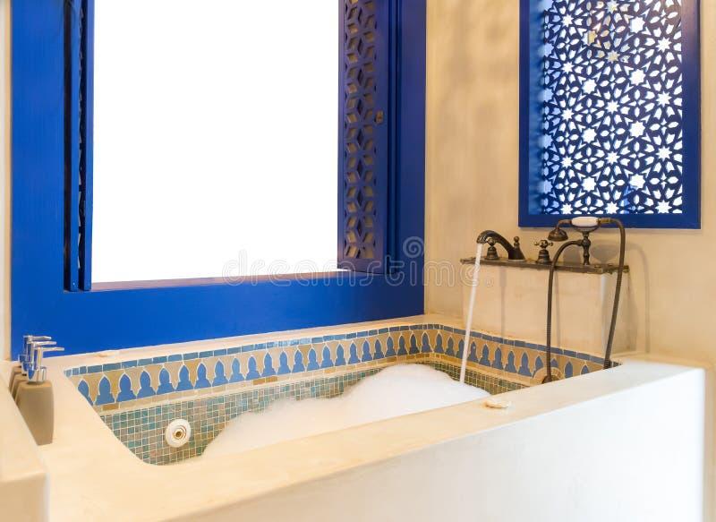 Weinlese-marokkanischer Steinjacuzzi mit blauem Fenster und Raum für Yo stockfotografie