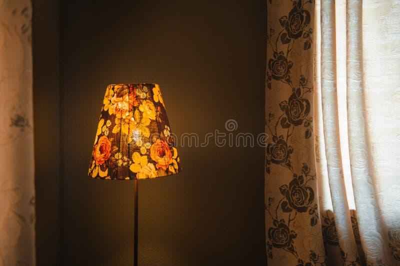 Weinlese-Schlafzimmerstehlampe, die in einer Ecke eines Raumes orange glüht lizenzfreie stockbilder