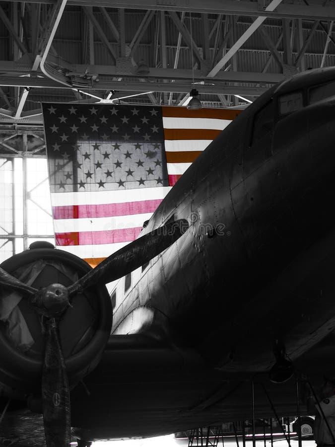 Weinlese-Schwarzweiss-Flugzeug mit amerikanischer Flagge stockfotografie