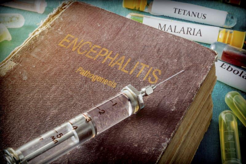 Weinlese-Spritze auf einem Buch der Gehirnentzündung stockbild