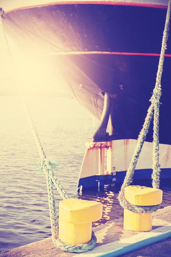 Weinlese stilisierte das gelbe festgemachte Schiffspollerholdingschiff stockfoto