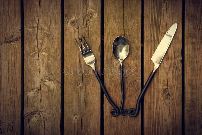 Weinlese-Tischbesteck - Gabel, Löffel und Messer aufgelockert auf hölzernem Backgroun stockfotos