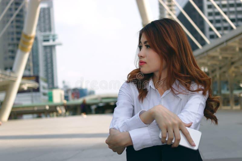 Weinlese tonte Bild der attraktiven jungen asiatischen Geschäftsfrau, die über etwas am Stadthintergrund denkt und träumt stockbilder