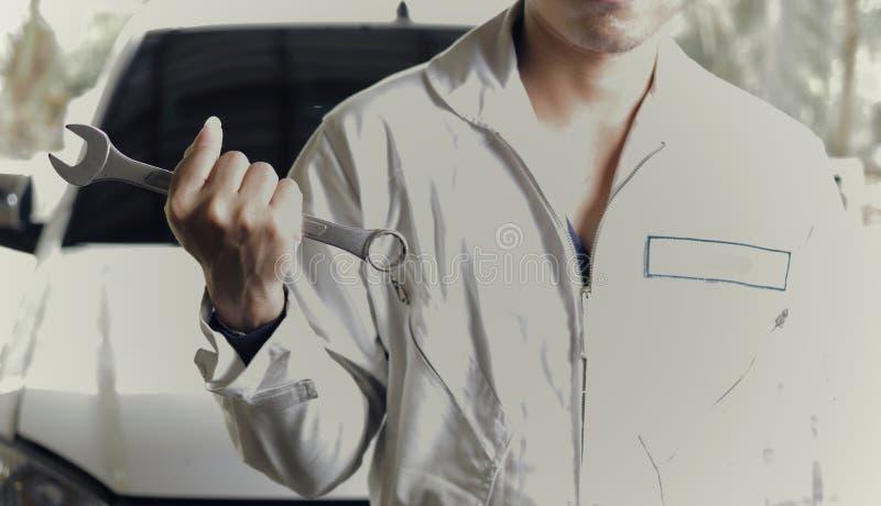 Weinlese tonte Bild des professionellen jungen Mechanikermannes im einheitlichen haltenen Schlüssel gegen Auto an der Reparaturga lizenzfreie stockfotografie