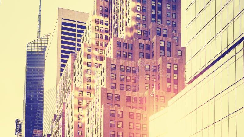 Weinlese tonte hohes Schlüsselbild von Wolkenkratzern gegen Sonne, NYC lizenzfreie stockfotos