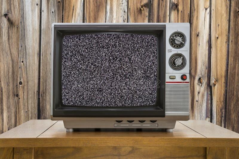 Weinlese-tragbares Fernsehen auf Tabelle mit statischem Schirm lizenzfreie stockbilder