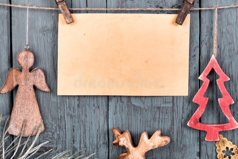 Weinlese-Weihnachtsdekorationen, die an der Schnur auf altem hölzernem Ba hängen stockfotografie