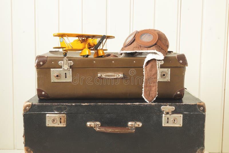 Weinleseabtönen Hintergrund der alten Retro- Koffer des Sturzhelmpilot- und -spielzeugsgelbes Metallflugzeugs zwei weißes hölzern lizenzfreies stockbild