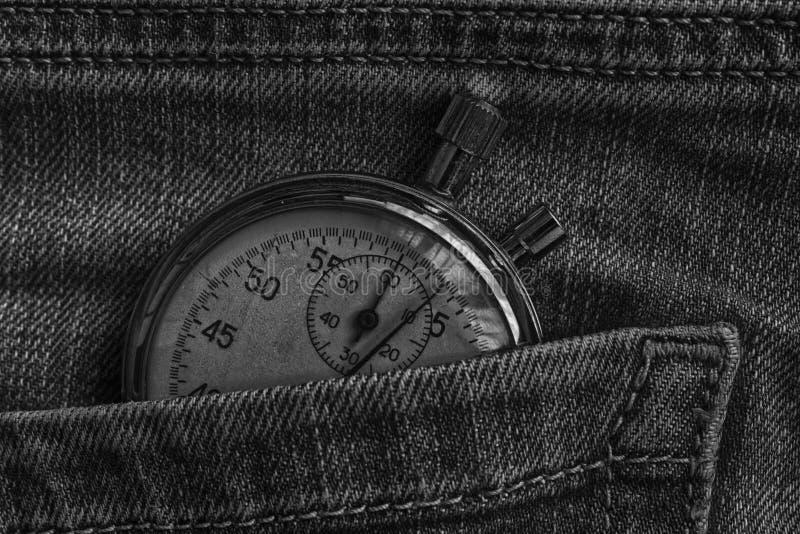 Weinleseantiquitäten Stoppuhr, in abgenutzten dunklen Jeans stecken, Wertmaßzeit, alte Uhrpfeilminute, zweite Genauigkeitstimer-A lizenzfreies stockfoto