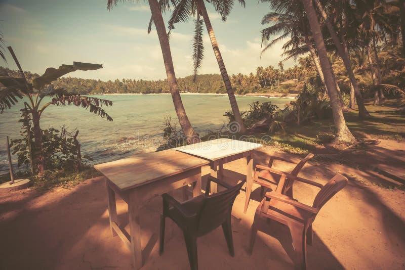 Weinleseartansicht der Tabelle auf Ozeanstrand mit Kokosnussbäumen herum Tropische Landschaft am Erholungsort lizenzfreie stockfotografie