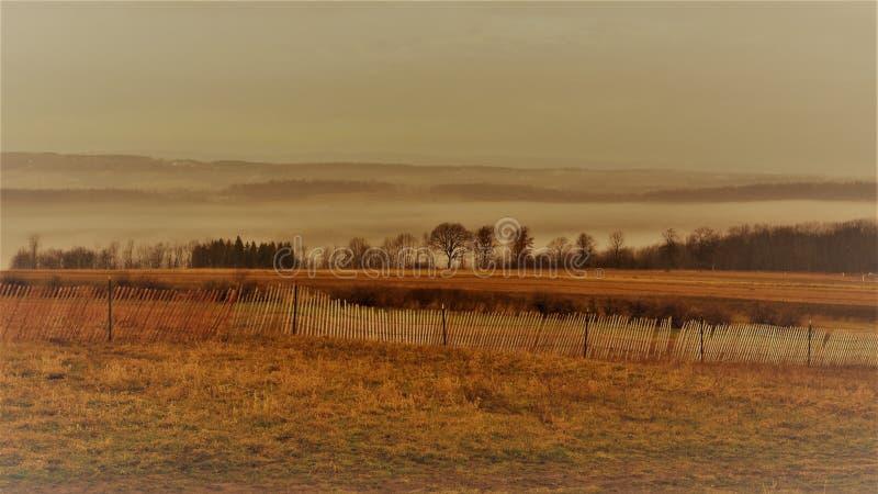 Weinleseartfoto des rustikalen hölzernen Schnee Zauns und Nebels auf dem Abhang stockfotos