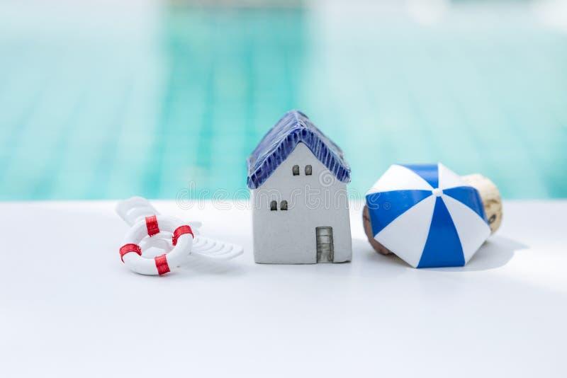 Weinleseartkeramisches Miniaturhaus mit Strandsatz über unscharfem blauem Swimmingpool-Wasserhintergrund lizenzfreie stockbilder