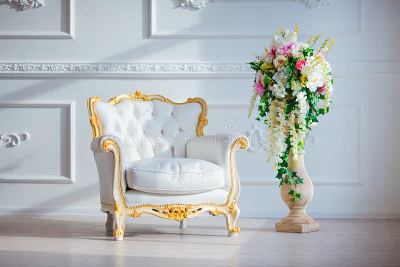 Weinleseartstuhl des weißen Leders im klassischen Innenraum mit großem Fenster und Frühling blüht stockfotografie
