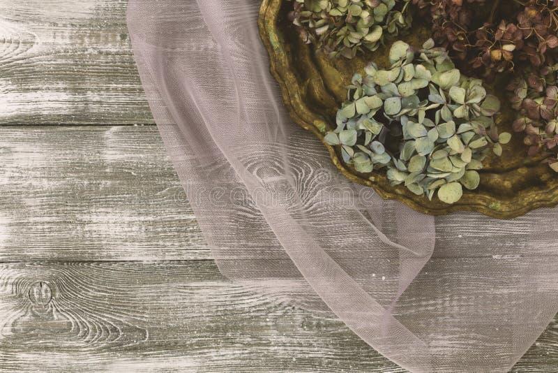 Weinlesebehälter mit getrockneten blauen Hortensieblumen auf einem purpurroten transparenten Tulle-Gewebe auf einer grauen Tabell lizenzfreies stockbild