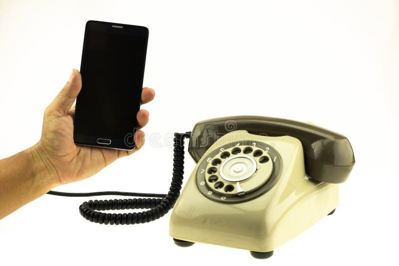 Weinlesebildart des neuen intelligenten Telefons mit altem Telefon auf weißem Hintergrund Neue Kommunikationstechnologie stockfotos