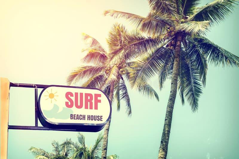 Weinlesebrandungs-Strandhaus Signage und KokosnussPalme auf blauem Himmel des tropischen Strandes stockfotos