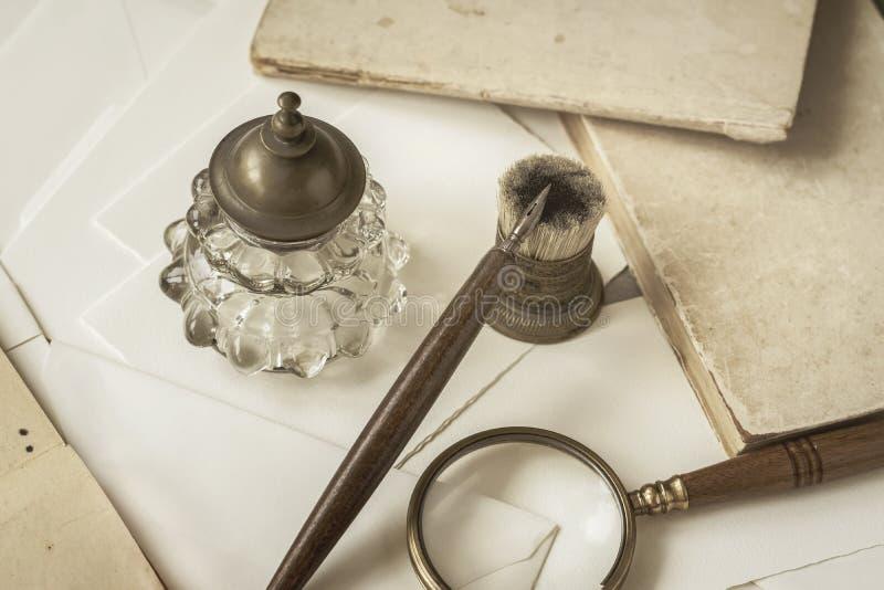 Weinlesebriefpapier, hölzerner Stift, Tintenfaß, Vergrößerungsglas und Umschläge, Buchstaben schließen oben Schreiben eines Brief lizenzfreies stockfoto
