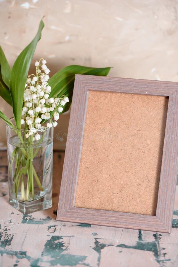 Weinleseeffekt auf Fotoblumenstrauß von Maiglöckchen und Raum simsen stockfoto