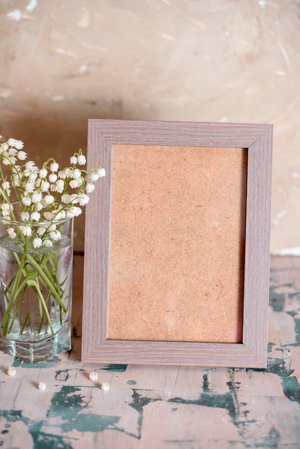 Weinleseeffekt auf Fotoblumenstrauß von Maiglöckchen und Raum simsen lizenzfreies stockfoto