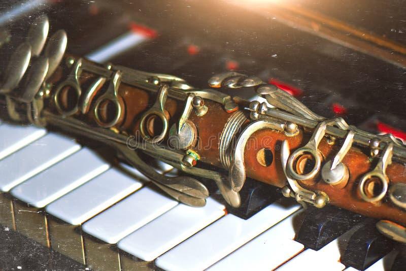 Weinleseeffektphotographie Antike Klarinette, die auf Klavierschlüssel sich lehnt lizenzfreie stockfotos