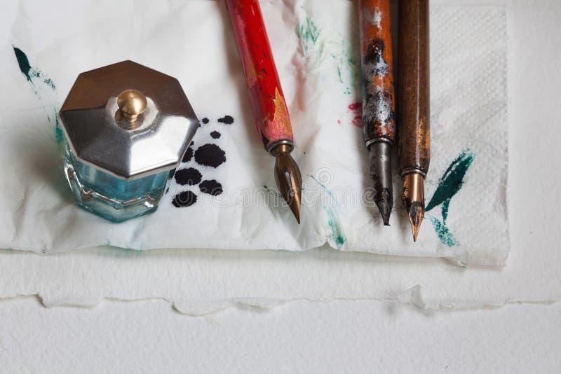 Weinlesefüllfederhalter mit Tintenfasskladdenserviette Strukturierter Hintergrund des Weißbuches Künstlerwerkstattkonzept Nahaufn lizenzfreies stockfoto