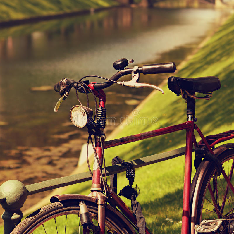 Weinlesefahrrad im Park nahe dem Zaun auf hellem sonnigem des Flusses stockfotografie