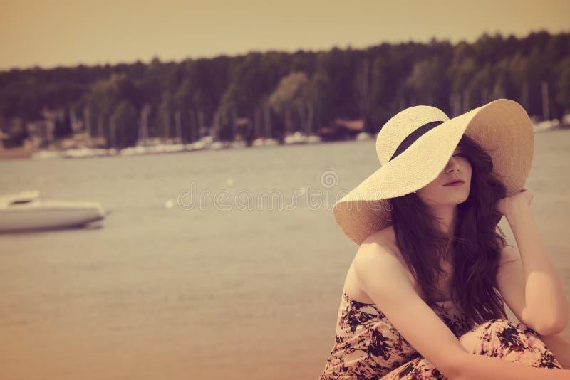 Weinlesefarbeffekt, süßes Porträt des Sommermädchens nahe See stockfoto