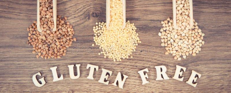 Weinlesefoto, Buchweizen- und Hirsegrützen mit Schaufel auf rustikalem Brett, gesunde und Gluten geben Lebensmittel frei stockbild