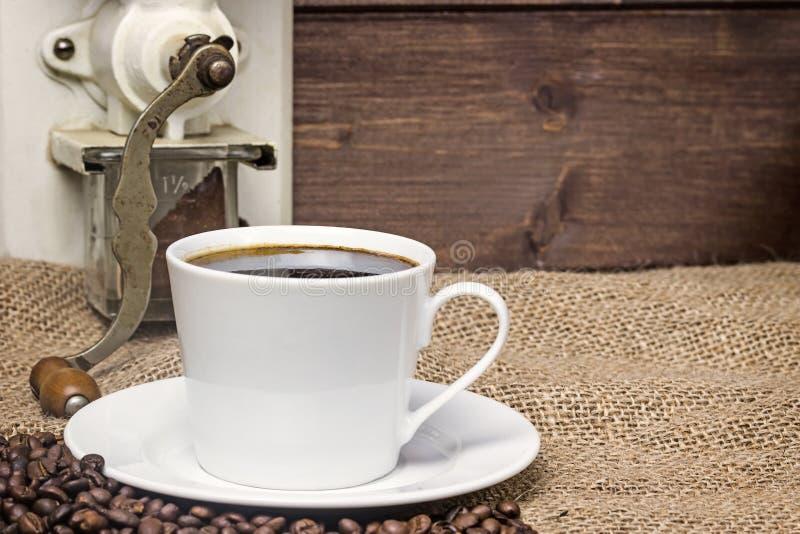 Weinlesefoto des Tasse Kaffees und der Kaffeemühle stockfoto