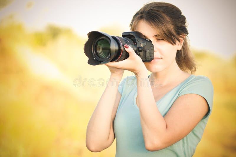 Weinlesefoto eines Fotografen der jungen Frau mit Kamera in der Hand lizenzfreies stockbild